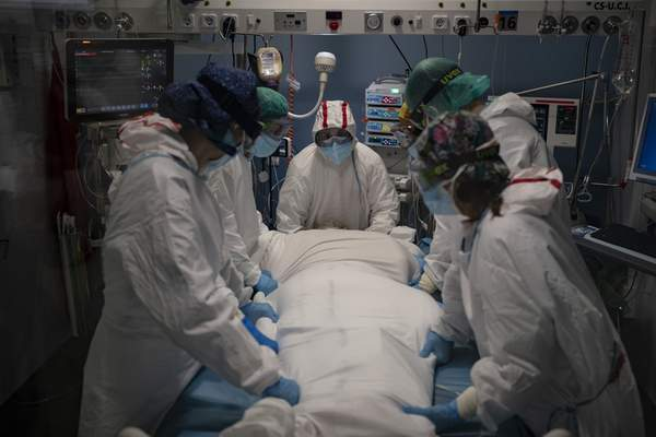 A medical team prepares to rotate a COVID-19 patient in the ICU of the Hospital del Mar, in Barcelona, Spain, Tuesday, Jan. 19, 2021. (AP Photo/Felipe Dana)