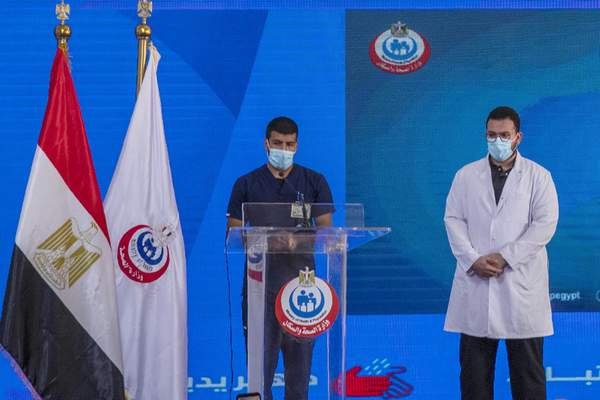 Nurse Ahmed Hamdan Zayed, left, and Dr. Abdel Menoim Selim, the first two Egyptians to receive the Sinopharm China-made COVID-19 vaccine, stand on a stage to answer questions during a press conference, at the Abu Khalifa Hospital in Ismailia, 120 km (75 miles) east of Cairo, Egypt, Sunday, Jan. 24, 2021. (AP Photo/Nariman El-Mofty)