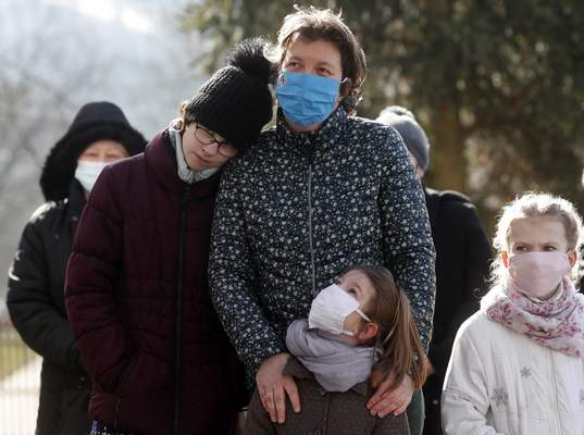 People, wearing masks for protection against the COVID-19 infection, stand outdoors during an outdoor Lutheran Church religious service in Csovar, Hungary, Sunday, Jan. 24, 2021. (AP Photo/Laszlo Balogh)