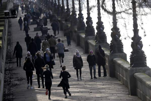 People exercise along the bank of the River Thames in London, Saturday, Jan. 23, 2021 during England's third national lockdown since the coronavirus outbreak began. (AP Photo/Kirsty Wigglesworth)