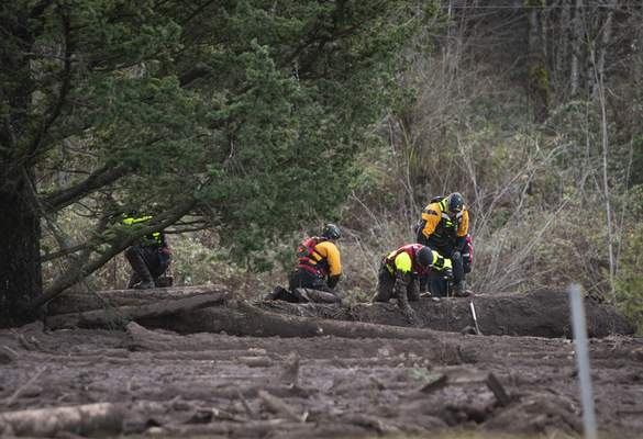 FILE - In this Thursday, Jan. 14, 2021 file photo, Search and rescue crews use metal rods to poke through the mud as they continue to search for a missing woman whose car was swept away by a landslide Wednesday in the Dodson area of the Columbia River Gorge, in Oregon. (Brooke Herbert/The Oregonian via AP, File)