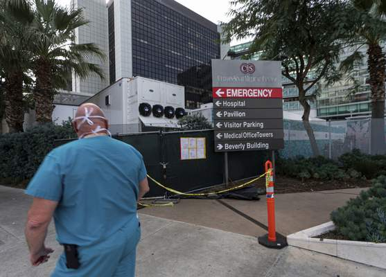 FILE - In this Jan. 7, 2021, file photo, a medical worker walks past a refrigerated trailer parked outside the Cedars-Sinai Medical Center in Los Angeles. (AP Photo/Damian Dovarganes, File)