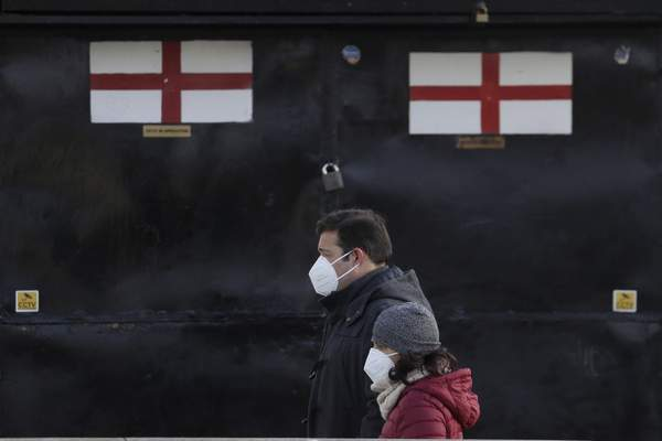Pedestrians pass a closed souvenir stand in London, Saturday, Jan. 23, 2021 during England's third national lockdown since the coronavirus outbreak began. (AP Photo/Kirsty Wigglesworth)