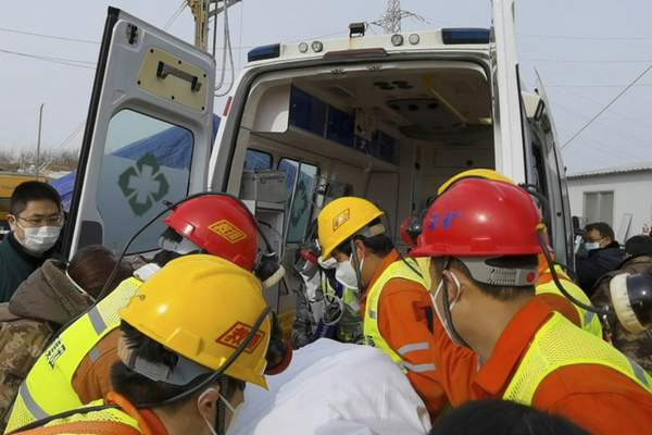 In this photo released by Xinhua News Agency, rescuers carry a miner who was trapped in a gold mine in Qixia City in east China's Shandong Province, Sunday, Jan. 24, 2021. (Luan Qincheng/Xinhua via AP)