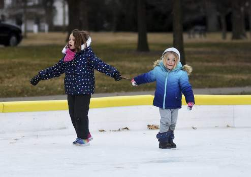 Katie Fyfe | The Journal Gazette Alexis Elser, 6, and Ellenor Colglazier, 4, play together on the ice rink at Lakeside Park on Sunday afternoon.