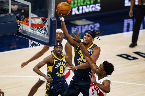 Indiana Pacers center Myles Turner (33) gets a basket over Toronto Raptors forward Stanley Johnson (5) during the first half of an NBA basketball game in Indianapolis, Monday, Jan. 25, 2021. (AP Photo/Michael Conroy)