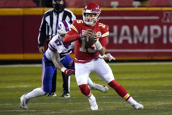 Kansas City Chiefs quarterback Patrick Mahomes (15) scrambles up field ahead of Buffalo Bills defensive end AJ Epenesa (57) during the first half of the AFC championship NFL football game, Sunday, Jan. 24, 2021, in Kansas City, Mo. (AP Photo/Jeff Roberson)
