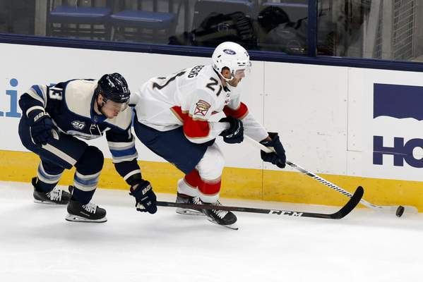 Florida Panthers forward Alex Wennberg, right, of Sweden, controls the puck in front of Columbus Blue Jackets forward Cam Atkinson during the first period of an NHL hockey game in Columbus, Ohio, Tuesday, Jan. 26, 2021. (AP Photo/Paul Vernon)