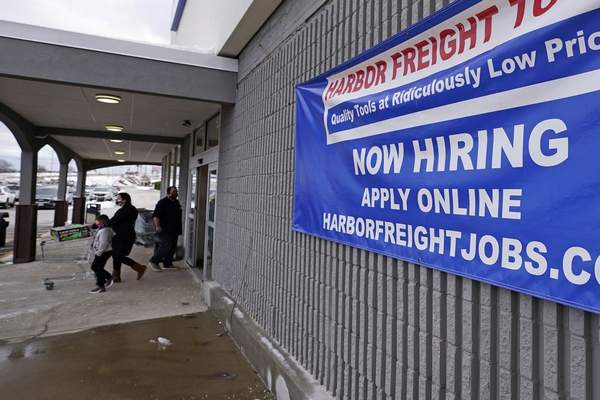 FILE - In this Dec. 10, 2020 file photo, a Now Hiring sign hangs on the front wall of a Harbor Freight Tools store in Manchester, N.H. (AP Photo/Charles Krupa, File)