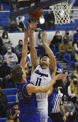Katie Fyfe | The Journal Gazette  Carroll junior Jalen Jackson takes a shot while Homestead junior Andrew Leeper defends him during the third quarter at Carroll High School on Friday.