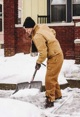 Katie Fyfe | The Journal Gazette  Jimme King shovels the sidewalk in front of his home in West Central Monday morning.