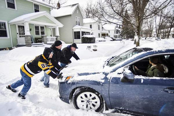 Katie Fyfe | The Journal Gazette  Dalton Welsh, Jim Owens and Mike Didier, left to right, help a neighbor who is stuck in a Columbia Avenue driveway get out Tuesday morning.