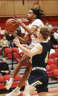 Katie Fyfe | The Journal Gazette  North Side senior Isaiah Moore shoots while Bishop Dwenger senior Xavier Nolan tries to stop him during the second quarter at North Side High School Friday.