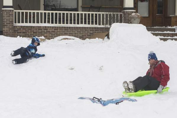 Michelle Davies | The Journal Gazette Katie Cochran takes turns with her son, Abraham, 5, sliding down a snow ramp in the front yard of their Florida Drive home Wednesday afternoon.