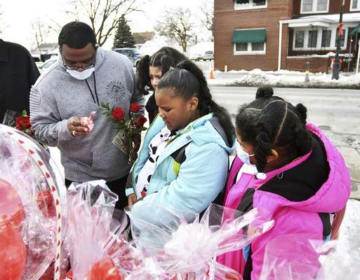 Katie Fyfe | The Journal Gazette  The Honor Family grabs a Valentines Day gift for their grandmother outside of the La Michoacana food truck on Wells Street Sunday afternoon.