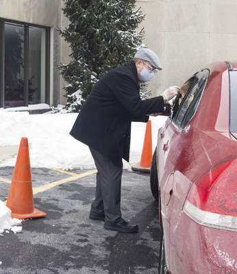 Michelle Davies | The Journal Gazette  Pastor Jason Morris of First Wayne United Methodist Church administers ashes to parishioners in their cars Wednesday afternoon. Church members were able to watch an online service and then follow it with drive-thru ashes for Ash Wednesday.
