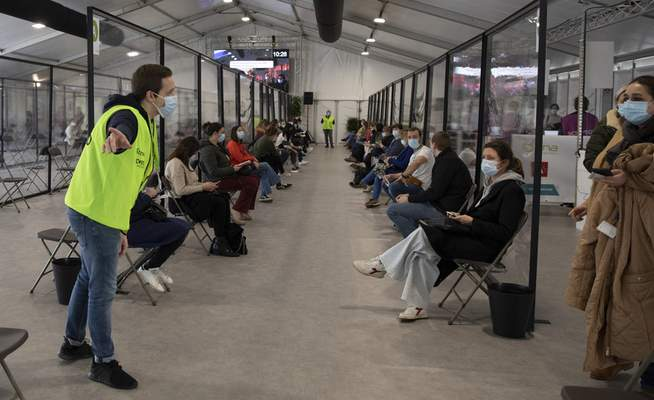 A steward directs people to seats in a waiting room after receiving an injection of the AstraZeneca coronavirus vaccine at the Vaccine Village in Antwerp, Belgium, on Friday, Feb. 19, 2021. (AP Photo/Virginia Mayo)