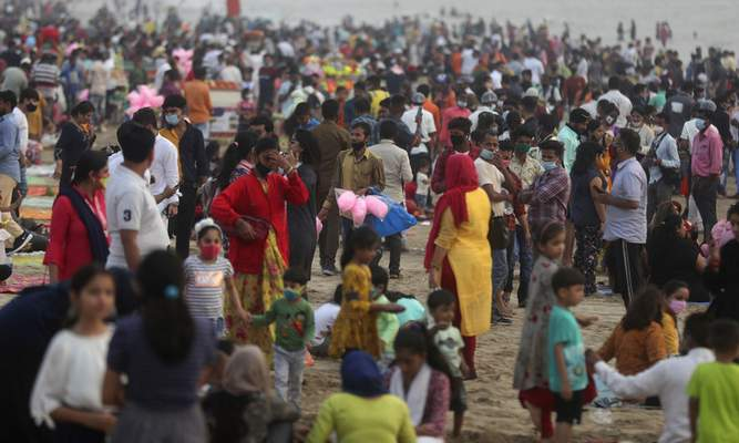 People crowd Juhu beach in Mumbai, India, Friday, Feb. 19, 2021. Health officials have detected a spike in COVID-19 cases in several pockets of Maharashtra state, including in Mumbai, the country's financial capital. (AP Photo/Rafiq Maqbool)