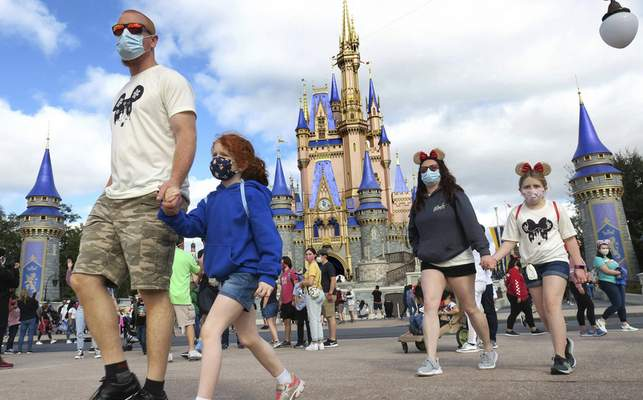 FILE - IN this Dec. 21, 2020 file photo, A family walks past Cinderella Castle in the Magic Kingdom, at Walt Disney World in Lake Buena Vista, Fla. To help celebrate the 50th anniversary of the opening of Walt Disney World in Florida, Mickey and Minnie are getting flashier threads and iconic structures such as Cinderella's Castle and the Tower of Terror are getting new lighting. Disney officials on Friday, Feb. 19, 2021, unveiled the first details on how Disney World will celebrate its milestone anniversary.(Joe Burbank/Orlando Sentinel via AP, File)