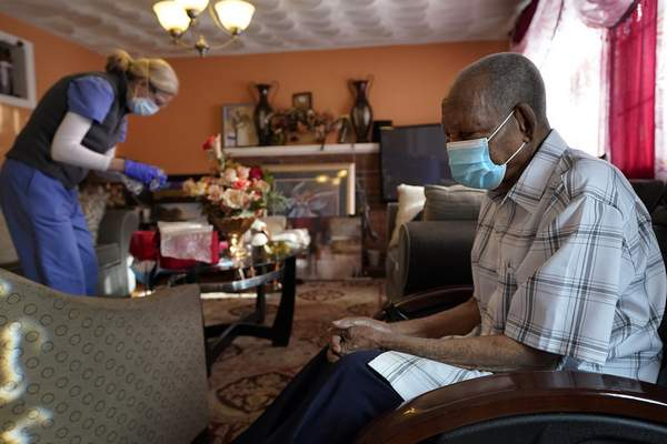 Edouard Joseph, 91, right, clasps his hands as geriatrician Megan Young, left, prepares to give him a COVID-19 vaccination, Thursday, Feb. 11, 2021, at his home in the Mattapan neighborhood of Boston. Millions of U.S. residents will need COVID-19 vaccines brought to them because they rarely or never leave home. Doctors and nurses who specialize in home care are leading this push and starting to get help from state and local governments around the country. (AP Photo/Steven Senne)
