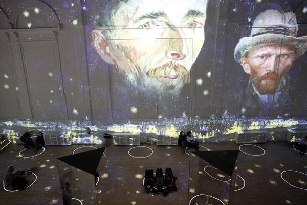 Patrons socially distance as they look at the moving images cast on the walls, floors and reflecting mirrors during a virtual display titled Immersive Van Gogh on Thursday, Feb. 18, 2021, at the Lighthouse ArtSpace, in Chicago. (AP Photo/Shafkat Anowar)