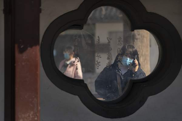 A woman wearing a face mask to protect against the spread of the coronavirus uses her smartphone at a public park in Beijing, Friday, Feb. 19, 2021. China has been regularly reporting no locally transmitted cases of COVID-19 as it works to maintain control of the pandemic within its borders. (AP Photo/Mark Schiefelbein)
