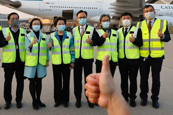 Secretary for Food and Health Sophia Chan Siu-chee, second left, and Secretary for the Civil Service Patrick Nip Tak-kuen, fourth right, pose as containers carrying Sinovac Biotech coronavirus disease (COVID-19) vaccines are unloaded from a Cathay Pacific Airways aircraft in Hong Kong, Thursday, Feb. 19, 2021. (Tyrone Siu/Pool Photo via AP)