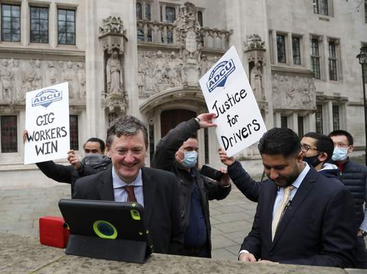Associated Press Uber drivers celebrate as they listen to the court decision outside the Supreme Court in London.