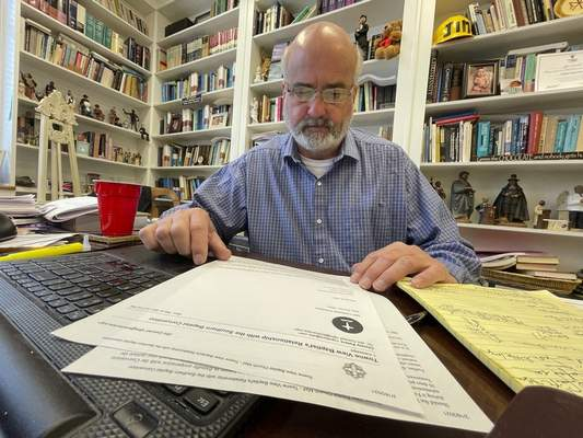 Jim Conrad, pastor of Towne View Baptist Church, looks at a copy of a letter from the Southern Baptist Convention's credentials committee on Thursday, Feb. 18, 2021, in Kennesaw, Ga. During an SBC meeting in late February, its executive committee will discuss a recommendation that Conrad's church be ousted from the SBC because it accepted LGBTQ people into its congregation. (AP Photo/Angie Wang)