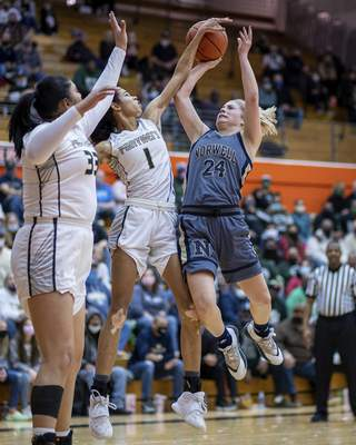 Norwell senior Kaylee Fuelling (24) draws contact from SB Washington sophomore Amiya Reynolds (1) during the Class 3A Semi-State Basketball Tournament at La Porte High School in La Porte, IN
