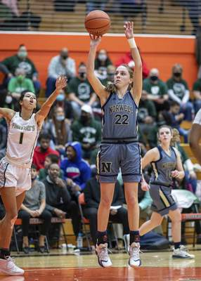Norwell senior Maiah Shelton (22) with a jumpshot as Washington sophomore Amiya Reynolds (1) defends in the first half of the Class 3A Semi-State matchup at La Porte High School in La Porte, IN.