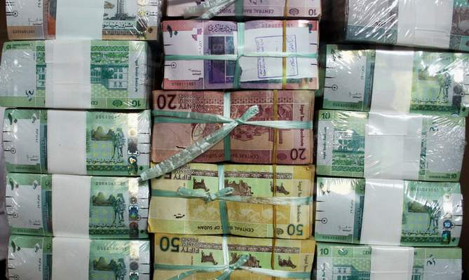 FILE - In this July 24, 2011, file photo, Sudan's new currency sits behind a window at the central bank in Khartoum, Sudan. (AP Photo/Abd Raouf, File)