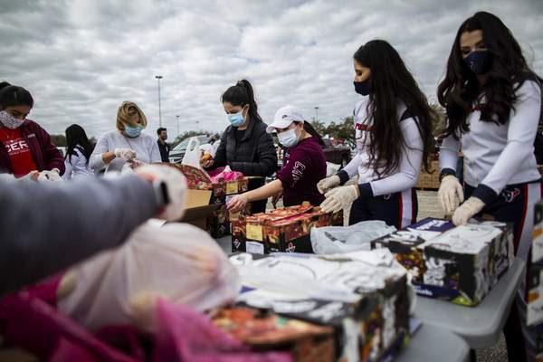 Associated Press Houston Texans cheerleaders and other volunteers pack food to distribute Sunday in Houston after frigid temperatures left the area depleted of resources.