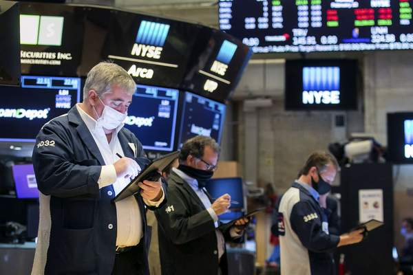 In this photo provided by the New York Stock Exchange, traders work on the floor, Monday Feb. 22, 2021. Investors remain focused on the future of global economies badly hit by COVID-19 and the potential for more stimulus to fix them. (Courtney Crow/New York Stock Exchange via AP)