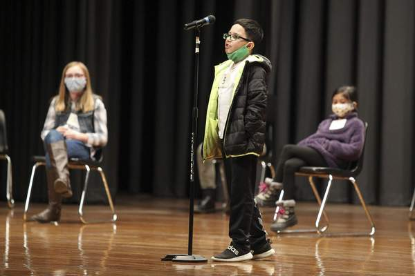 Giovanni Flores, a student at Rankin Elementary School, competes in the Tupelo Public School Disctict and Lee County Spelling Bee on Thursday, Jan. 14, 2021, at the Civic Auditorium of Tupelo Middle School in Tupelo, Miss. Mason Cordell, a seventh grader at Tupelo Middle School was this year's winner. (Adam Robison/The Northeast Mississippi Daily Journal via AP)