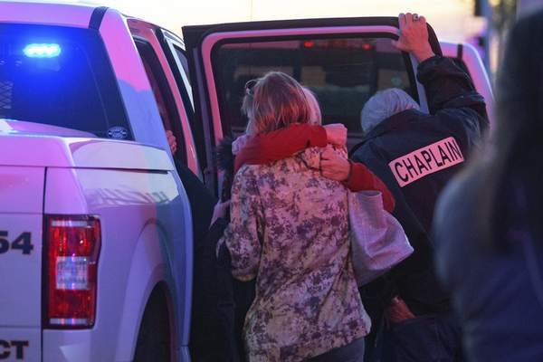 A Jefferson Parish Sheriff's Office Chaplain stands next to two women hugging including one who was wearing a Jefferson Gun Outlet shirt at the scene of a multiple fatality shooting at the Jefferson Gun Outlet in Metairie, La. Saturday, Feb. 20, 2021. (AP Photo/Matthew Hinton)