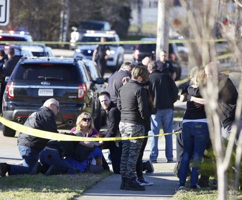 People are comforted by law enforcement as the Jefferson Parish Sheriff's Office deputies investigate a shooting at the Jefferson Gun Outlet in Metairie, La. Saturday, Feb. 20, 2021. (Sophia Germer/The Times-Picayune/The New Orleans Advocate via AP)