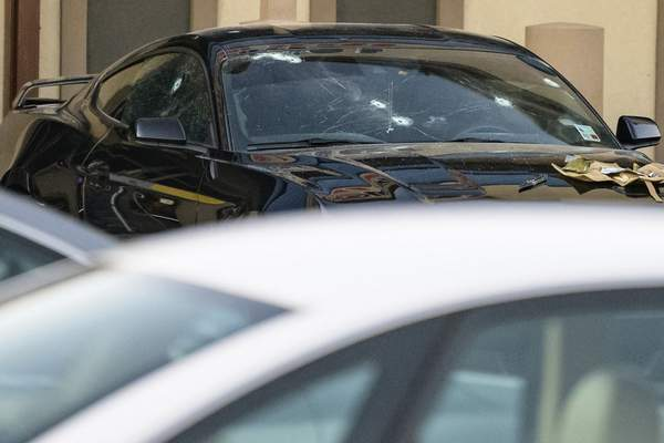 Bullet holes are seen on a vehicle at the scene of a multiple fatality shooting at the Jefferson Gun Outlet in Metairie, La. Saturday, Feb. 20, 2021. (AP Photo/Matthew Hinton)