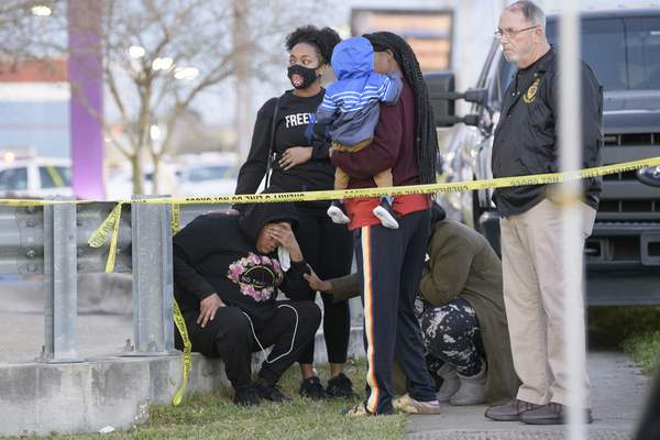People react at the scene of a multiple fatality shooting at the Jefferson Gun Outlet in Metairie, La. Saturday, Feb. 20, 2021. (AP Photo/Matthew Hinton)