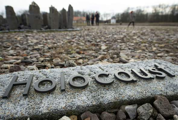 FILE - In this Monday, Jan. 27, 2020 file photo people walk behind the writing 'Holocaust' during the international Holocaust remembrance day in the former the Nazi concentration camp Buchenwald near Weimar, Germany. (AP Photo/Jens Meyer, file)