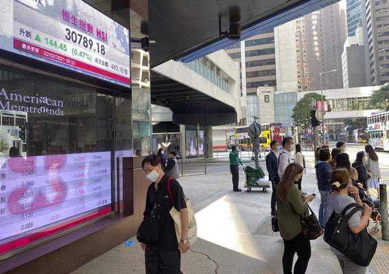 People walk past a bank's electronic board showing the Hong Kong share index in Hong Kong Monday, Feb. 22, 2021. (AP Photo/Vincent Yu)
