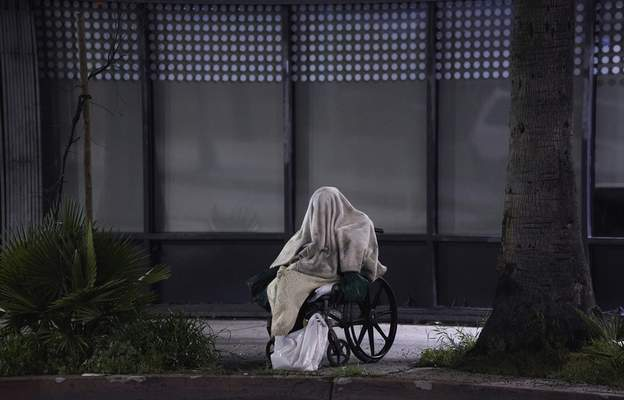 A homeless person sits on a wheelchair under rainy weather on Sunset Blvd., in the Echo Park neighborhood of Los Angeles Monday, April 6, 2020. (AP Photo/Damian Dovarganes)