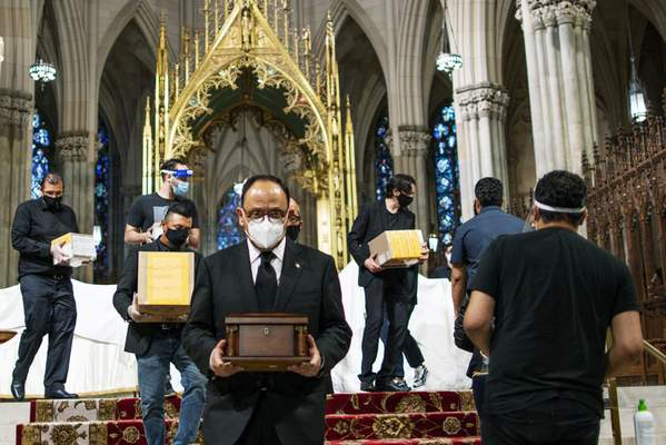 Jorge Islas Lopez, Consul General of Mexico, and others carry the remains of loved ones following the blessing of the ashes of Mexicans who died from COVID-19 at St. Patrick's Cathedral, Saturday, July 11, 2020, in New York. The ashes were blessed before they were repatriated to Mexico. (AP Photo/Eduardo Munoz Alvarez)