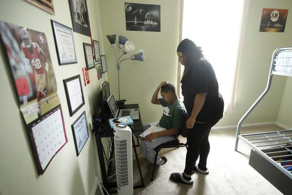 Lila Nelson watches as her son, Rise University Preparatory sixth-grader Jayden Amacker, watch an online class in his room at their home in San Francisco, April 9, 2020. (AP Photo/Jeff Chiu)