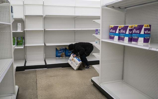 Deanna Butts reaches for one of the last packages of toilet paper at Target in the Tenleytown area of Washington, Tuesday, March 17, 2020. Supplies are restocked as trucks come in but the coronavirus outbreak caused a shortage of some items. (AP Photo/Carolyn Kaster)
