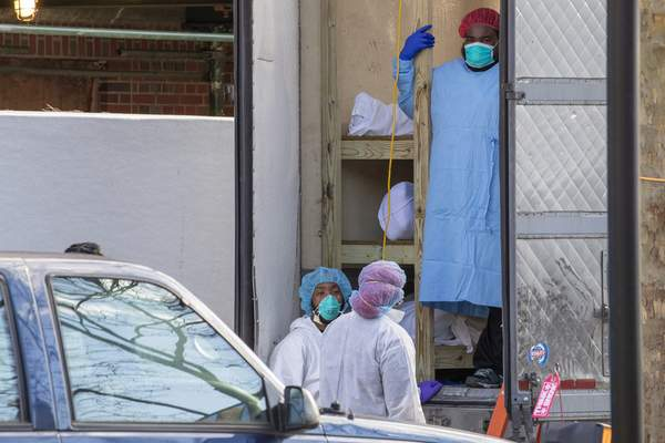 Medical personnel prepare to transport a body from a refrigerated container at Kingsbrook Jewish Medical Center, Wednesday, April 8, 2020, in the Brooklyn borough of New York. (AP Photo/Mary Altaffer)