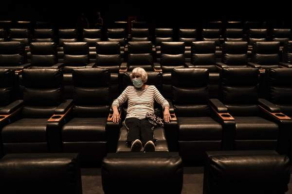 Karen Speros, 82, waits for a movie to start at a Regal movie theater in Irvine, Calif., Tuesday, Sept. 8, 2020, after California Gov. Gavin Newsom relaxed coronavirus restrictions in some counties. (AP Photo/Jae C. Hong)