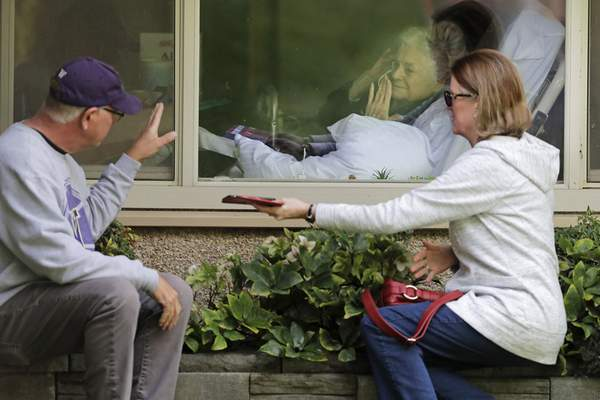 Judie Shape, center, who had tested positive for the coronavirus, blows a kiss to her son-in-law, Michael Spencer, left, as Shape's daughter, Lori Spencer, right, looks on, Wednesday, March 11, 2020, as they visit on the phone and look at each other through a window at the Life Care Center in Kirkland, Wash., near Seattle. In-person visits were not allowed at the nursing home. (AP Photo/Ted S. Warren)