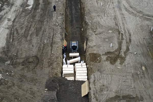 Workers wearing personal protective equipment bury bodies during the coronavirus pandemic in a trench on Hart Island in the Bronx borough of New York on Thursday, April 9, 2020. (AP Photo/John Minchillo)