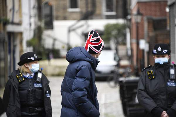 A member of the public wearing a Union Flag themed hat walks past the side entrance of the King Edward VII Hospital in London, Sunday, Feb. 21, 2021. (AP Photo/Alberto Pezzali)